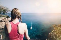 Hintere Ansicht der jungen Frau in der Sportkleidung, die Meer betrachtet stockfoto