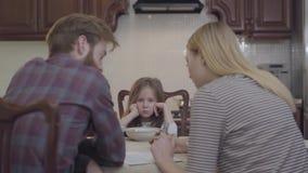 Hintere Ansicht der jungen Frau und des Mannes, die am Tisch hat die Frühstückseltern besprechen wichtige Dinge sitzt Kleine Ball stock video