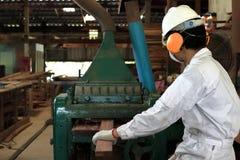 Hintere Ansicht der jungen hölzernen Arbeitskraft in der weißen Sicherheitsuniform, die mit Hobelmaschine in der Fabrik arbeitet lizenzfreies stockfoto