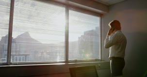 Hintere Ansicht der jungen kaukasischen männlichen Exekutive, die am Handy in einem modernen Büro 4k spricht stock video footage