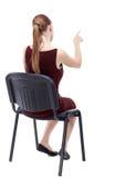 Hintere Ansicht der jungen Schönheit sitzend auf Stuhl und pointin Lizenzfreie Stockfotografie