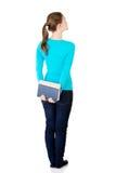 Hintere Ansicht der jungen Studentenfrau, die ein altes Buch hält. Lizenzfreie Stockbilder