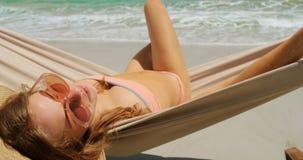 Hintere Ansicht der kaukasischen Frau entspannend in einer Hängematte am Strand 4k stock video footage