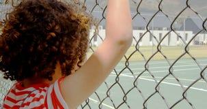 Hintere Ansicht der Mischrasseschulmädchenstellung nahe Maschendrahtzaun in der Schule 4k stock video footage