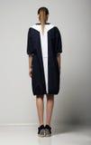 Hintere Ansicht der modischen Chichi Frau im Weiß-schwarzen Kontrast-Regenmantel. Vogue Stockfotografie