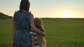 Hintere Ansicht der Mutter kommend und ihre kleine blonde Tochter umarmend, stehend mitten in Weizen- oder Roggenfeld stock footage