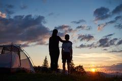 Hintere Ansicht der Mutter umarmt ihren Sohn nahe Zelt auf Berg Ansicht der Sonne genießend Lizenzfreie Stockfotografie