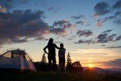 Hintere Ansicht der Mutter umarmt ihren Sohn nahe Zelt auf Berg Ansicht der Sonne genießend Stockbild