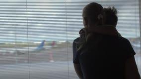 Hintere Ansicht der Mutter und des Sohns, die in das Fenster auf der Flugzeugrollbahn, Amsterdam, die Niederlande stehen und aufp stock video footage