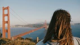 Hintere Ansicht der Nahaufnahme geschossen von der jungen touristischen Frau mit dem Haar, das im Wind epischen Sonnenuntergang g stock video footage