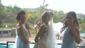 Hintere Ansicht der perfekten Braut und ihrer zwei Brautjungfern in den blauen am Balkon stehenden, drehenden, wellenartig bewege stock video