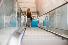 Hintere Ansicht der Schönheitsfrau reisend und ihr Gepäck auf Rolltreppe halten stockfotografie