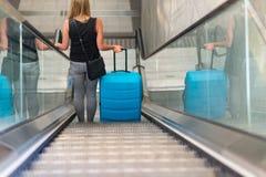 Hintere Ansicht der Schönheitsfrau reisend und ihr Gepäck auf Rolltreppe halten stockbilder