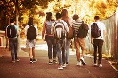 Hintere Ansicht der Schule scherzt das Gehen auf Straße im Campus stockbild
