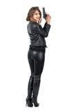 Hintere Ansicht der sexy gefährlichen Frau, die einen Gewehrdrehungskopf hält und an der Kamera lächelt Lizenzfreie Stockfotos