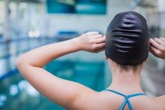 Hintere Ansicht der Sitzfrau setzend auf Schwimmenkappe Stockfotos