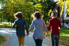 Hintere Ansicht der sorglosen Mutter und der Kinder, die in den Park laufen stockfotografie