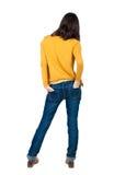 Hintere Ansicht der Stellung der jungen schönen Brunettefrau im Gelb Stockfoto