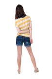 Hintere Ansicht der Stellung der jungen schönen Brunettefrau im Gelb Lizenzfreies Stockfoto