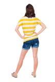 Hintere Ansicht der Stellung der jungen schönen Brunettefrau im Gelb Stockbild