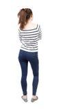 Hintere Ansicht der Stellung der jungen Schönheit in den Jeans Lizenzfreie Stockfotografie