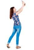 Hintere Ansicht der Stellung der jungen Schönheit, die ein bewegliches pho verwendet Stockbild
