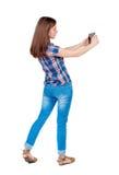 Hintere Ansicht der Stellung der jungen Schönheit, die ein bewegliches pho verwendet Lizenzfreie Stockfotos