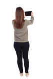 Hintere Ansicht der Stellung der jungen Schönheit, die ein bewegliches pho verwendet Stockfotografie
