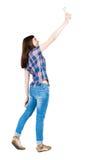 Hintere Ansicht der Stellung der jungen Schönheit und der Anwendung eines Mobiles Lizenzfreie Stockbilder