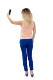 Hintere Ansicht der Stellung der jungen Schönheit und der Anwendung eines Mobiles Stockfoto