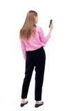 Hintere Ansicht der Stellung der jungen Schönheit und der Anwendung eines Mobiles Stockfotos