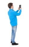 Hintere Ansicht der Stellung des jungen Mannes mit Tablet-Computer in der Hand Stockbilder