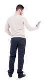 Hintere Ansicht der Stellung des jungen Mannes mit Tablet-Computer in der Hand Stockfotos