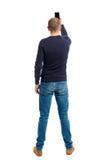Hintere Ansicht der Stellung des jungen Mannes und der Anwendung eines Handys Lizenzfreie Stockfotografie