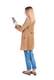 Hintere Ansicht der Stellung des jungen schönen Mädchens mit Tablet-Computer Stockbilder