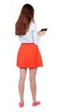 Hintere Ansicht der Stellung des jungen schönen Mädchens mit Tablet-Computer Lizenzfreies Stockbild