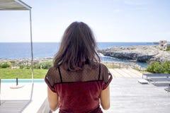Hintere Ansicht der Stellung der jungen Frau auf der Terrasse, die weg zum Seehorizont an einem sonnigen Tag schaut lizenzfreie stockfotografie