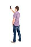Hintere Ansicht der Stellung von jungen Männern und der Anwendung eines Handys Lizenzfreies Stockbild