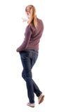 Hintere Ansicht der Zeigefrau. schönes blondes Mädchen in den Jeans Stockfotografie