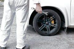 Hintere Ansicht des überzeugten Automobilmechanikers im weißen einheitlichen haltenen Schlüssel in seinem übergibt bereites zur R Stockfotografie