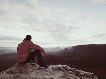 Hintere Ansicht des alleinwanderers in der dunkelroten Kleidung im Freien, die auf Felsen sitzt Stockfoto