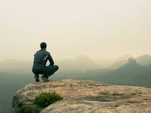 Hintere Ansicht des alleinwanderers in der dunklen Klage im Freien sitzen auf dem Rand Scharfe felsige Spitze über Gebirgstal Lizenzfreies Stockfoto