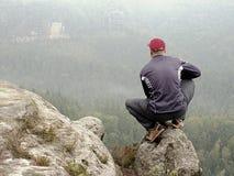 Hintere Ansicht des alleinwanderers in der dunklen Klage im Freien sitzen auf dem Rand Scharfe felsige Spitze über Gebirgstal Stockbild