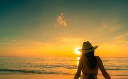 Hintere Ansicht des Asiatinabnutzungsbikinis und Strohhut sitzen auf Sandstrand, Feiertag am tropischen Paradiesstrand sich zu en stockfotos