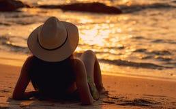 Hintere Ansicht des Asiatinabnutzungsbikinis und -strohhutes, die sich auf Sandstrand Feiertag, am tropischen Strand sich zu ents lizenzfreies stockfoto