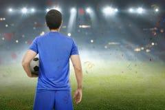 Hintere Ansicht des asiatischen Fußballspielers, der mit dem Ball steht lizenzfreies stockbild