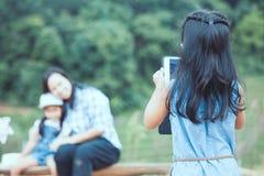 Hintere Ansicht des asiatischen Kindermädchens benutzt die Tablette, die ein Foto macht lizenzfreies stockfoto