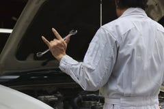 Hintere Ansicht des Berufsmechanikermannes, der ich liebe dich Schlüssel und seine Hand mit Zeichen mit Auto in der offenen Haube Lizenzfreie Stockfotografie