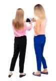 Hintere Ansicht des Blickes der jungen Frau zwei auf das intelligente Telefon Lizenzfreie Stockbilder