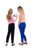 Hintere Ansicht des Blickes der jungen Frau zwei auf das intelligente Telefon Stockbild